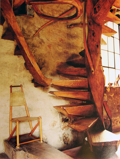 Wharton Esherick's stair encased in worn plaster walls in his home in PA from Handcrafted Modern by Leslie Williamson