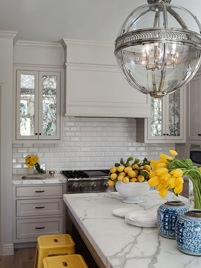The ever talented Benjamin Dhong added glamour and visual pop with kitchen cabinets faced in heavily antiqued mirror. Photo via La Dolce Vita Blog