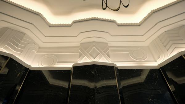 White plaster friezes designed by SuperStrata for the Walker Tower Lobby top lush, black stone walls.